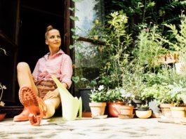 kobieta w kaloszach siedząca w drzwiach domku na działce
