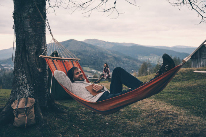 mężczyzna czytający książkę na hamaku w górach