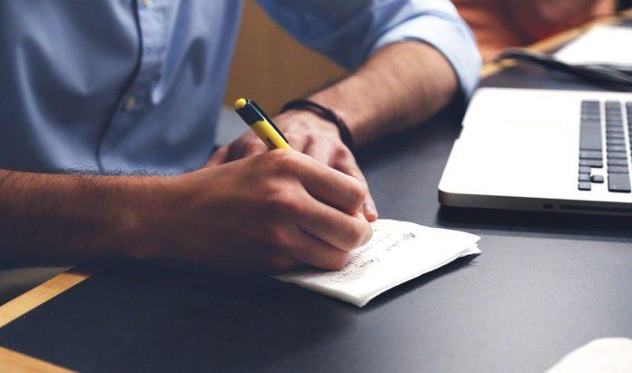 mężczyzna wykonujący odręczne notatki