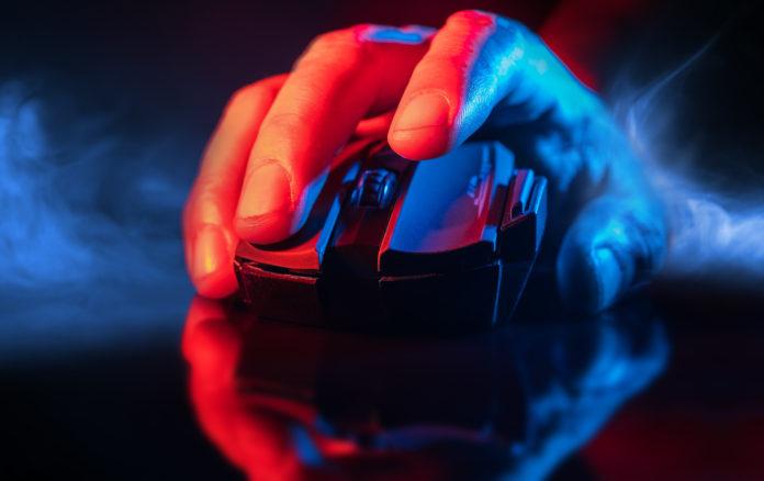 męska dłoń na myszce gamingowej