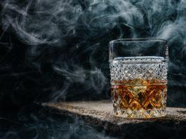 szklanka whisky na drewnianym stole w zadymionym pomieszczeniu