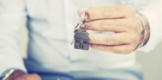 wyciągnięta męska dłoń trzymająca klucze do mieszkania