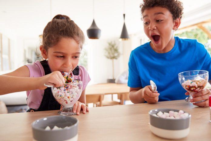 dwójka dzieci jedząca lody z pucharków