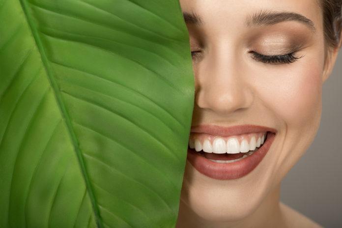 kobieta w makijażu obok zielonego liścia
