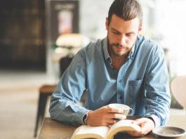 mężczyzna czytający książkę w kawiarni