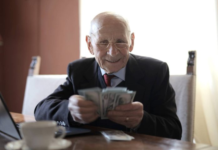 starszy człowiek liczący pieniądze