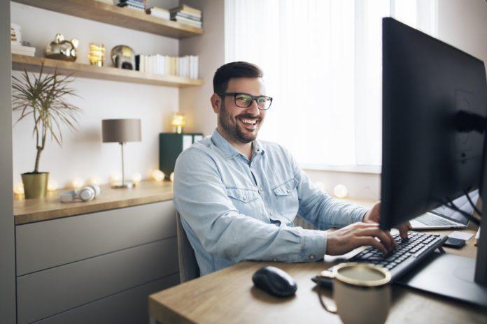 mężczyzna pracujący przy komputerze w domu