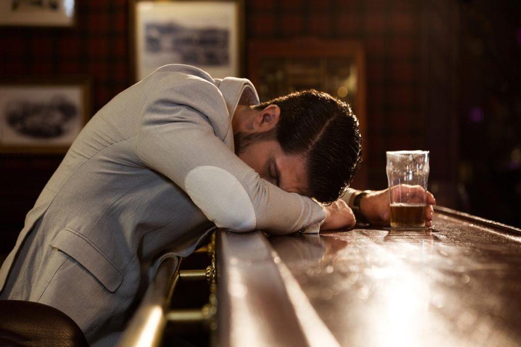 młody człowiek śpiący na barze przy szklance alkoholu