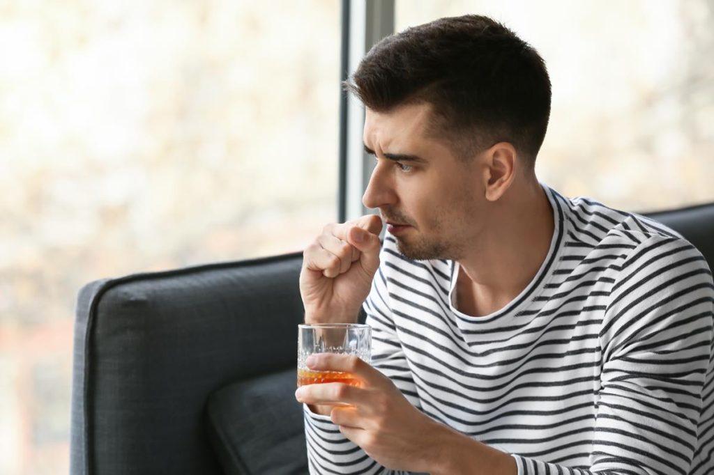 smutny mężczyzna pijący alkohol przy oknie