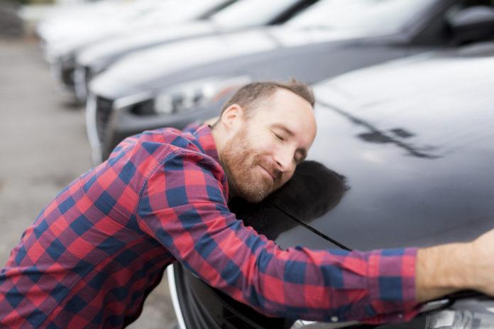 mężczyzna przytulający się do samochodu