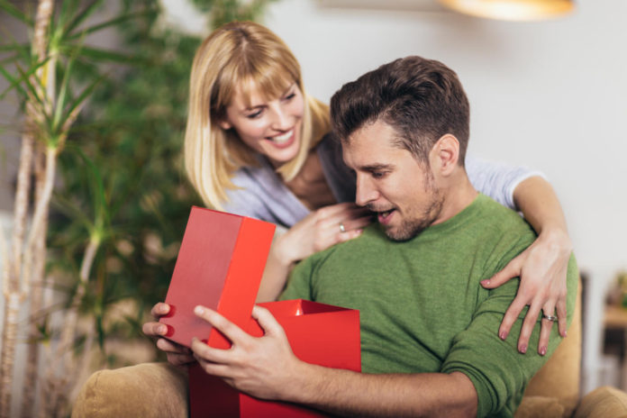zaskoczony mężczyzna otrzymujący prezent od kobiety