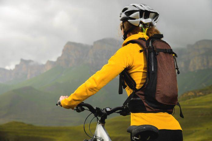 kobieta z lekkim plecakiem na rowerze w górach