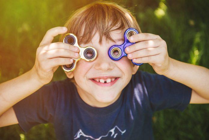 zadowolony chłopiec ze spinnerami