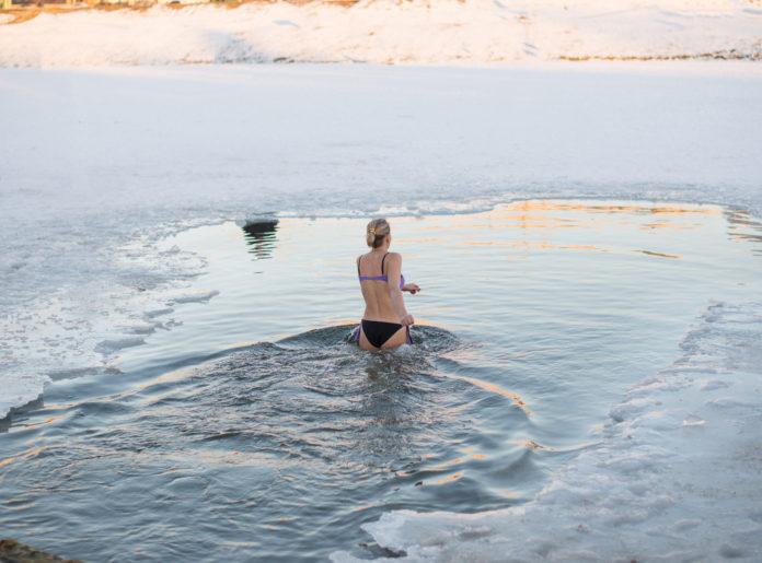 kobieta wchodząca do lodowatej wody morsowanie