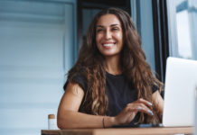 piękna uśmiechnięta kobieta z długimi włosami przed laptopem