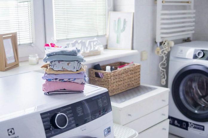 pralnia domowa ubrania złożone w kostkę położone na pralce