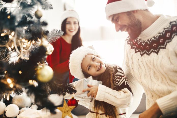 rodzina otwierająca prezenty pod choinką