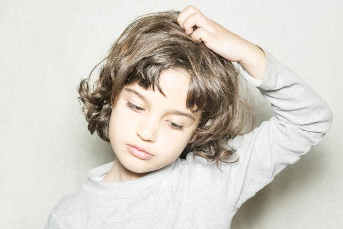 chłopiec drapiący się po głowie