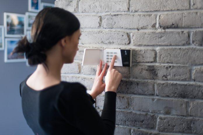 kobieta włączająca system alarmowy