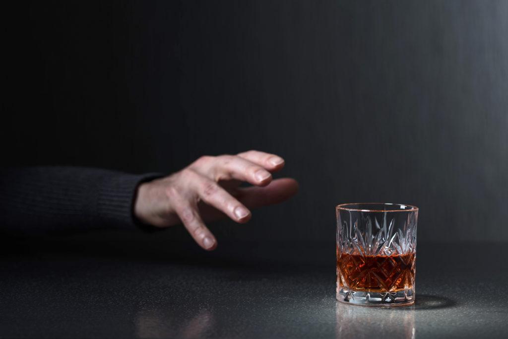 męska dłoń sięgająca po alkohol