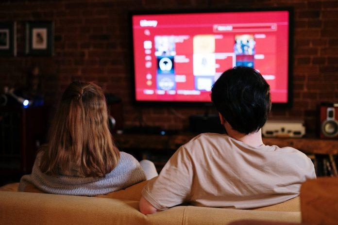 kino domowe para przed telewizorem