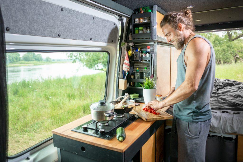 hipster gotujący w kamperze