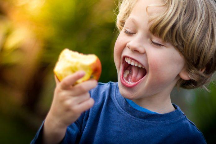chłopiec jedzący jabłko