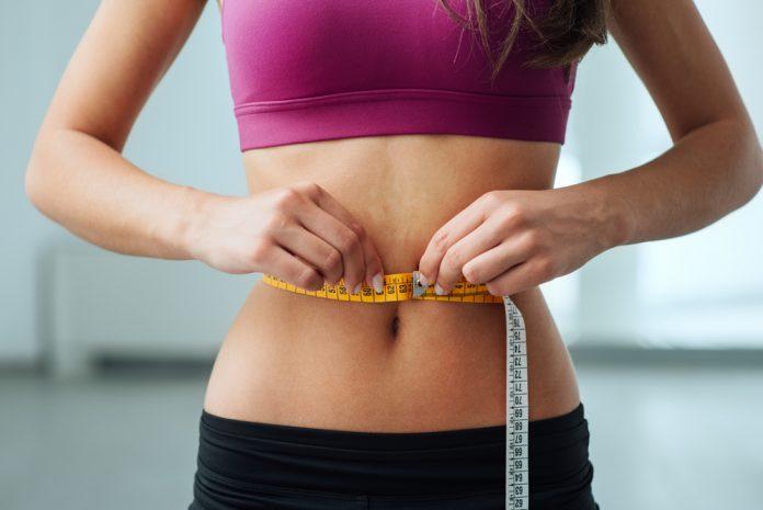 kobieta mierząca swój brzuch