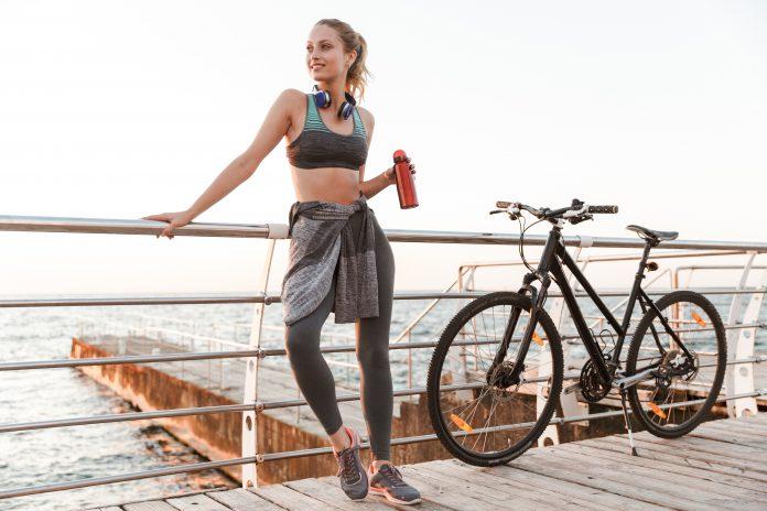 młoda kobieta na rowerze z bidonem