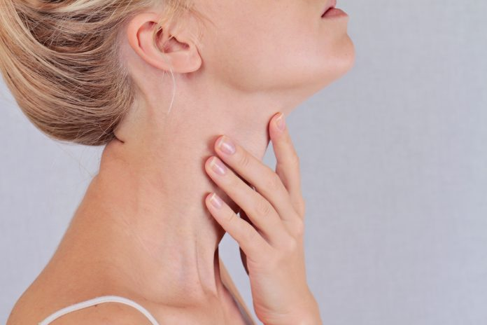 Tyreotropina - kobieta dotykająca szyi i sprawdzająca tarczycę