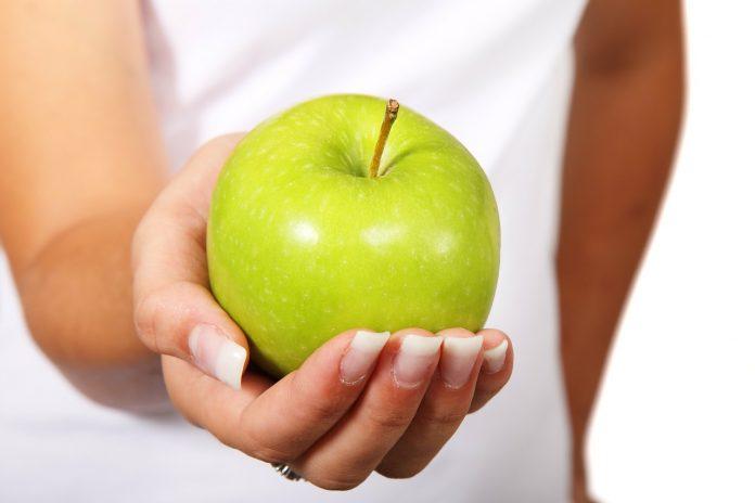 zielone jabłko na kobiecej dłoni