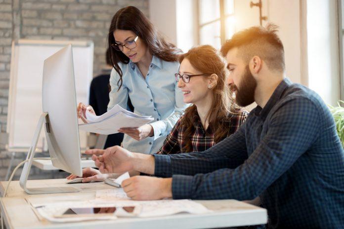 młodzi ludzie w biurze przed komputerem