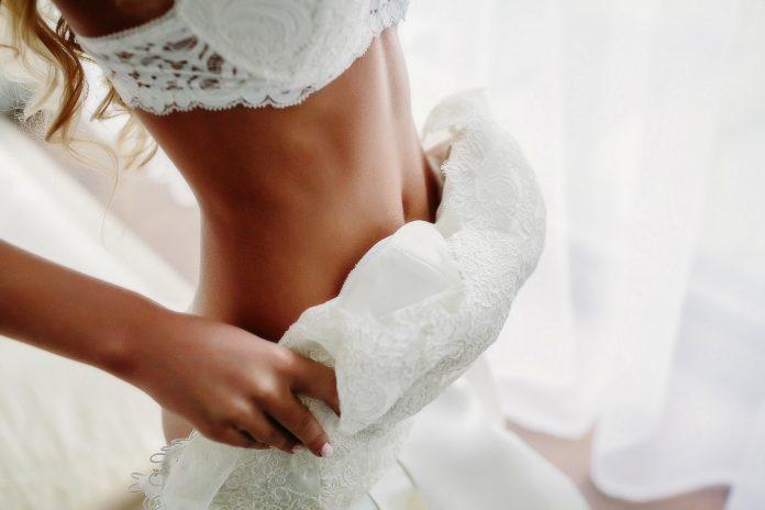 panna młoda zakładająca suknię ślubną