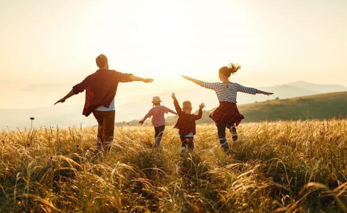 rodzina biegnąca przez łąkę w słońcu