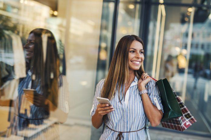 kobieta sprawdzająca ranking produktów w smartfonie